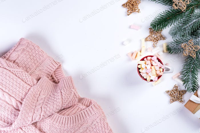 Chocolate with marshmallow sweets in cup, pink knitted sweater and fir tree for Christmas holiday