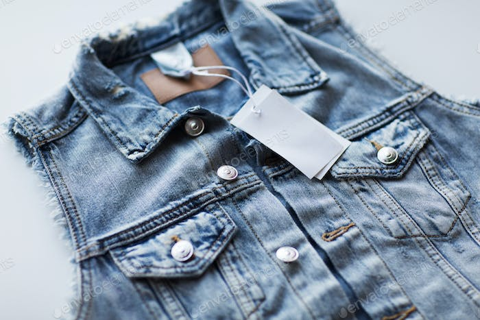 close up of denim waistcoat with price tag