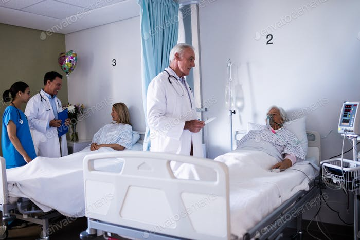 Male doctor interacting with senior patient in the ward