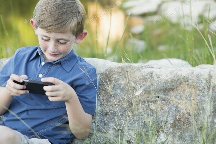 Ein kleiner Junge im Freien sitzt an einem Felsen gelehnt, mit einem elektronisch Handspiel.