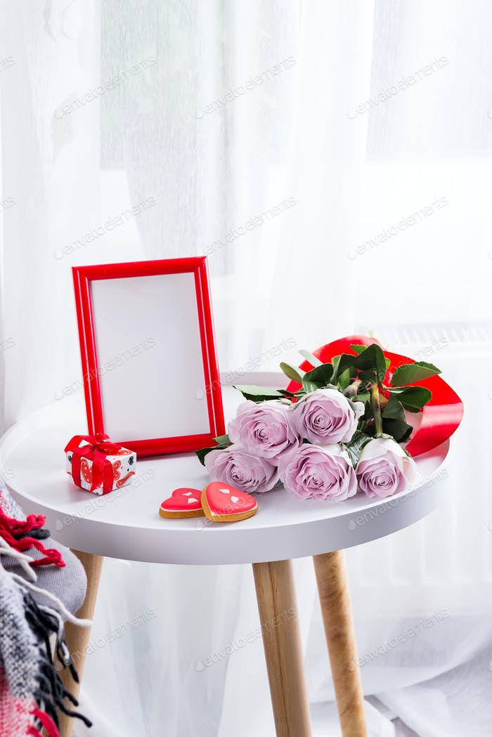 Homemade Valentines day heart cookies, pink roses and red frame on white table near window, copy