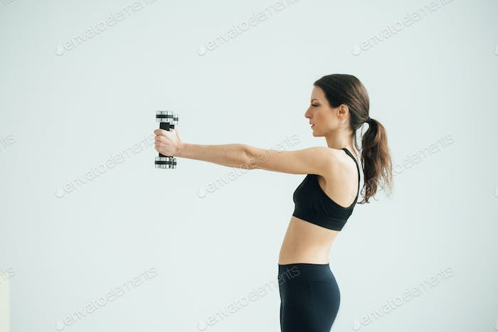 Young beautiful sporty woman home doing sports training