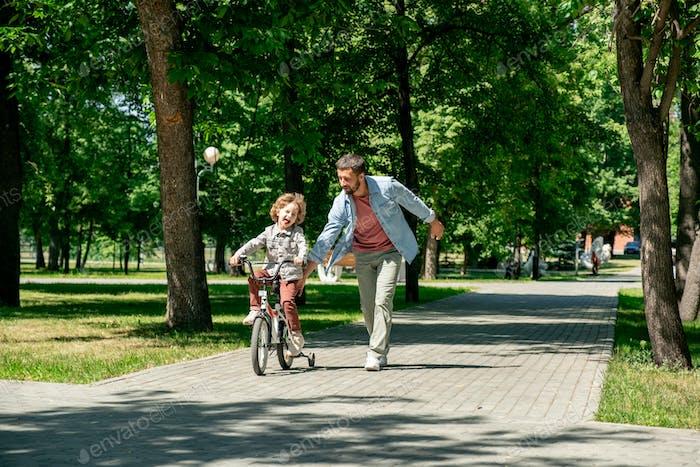 Joyful Kind Fahrrad fahren mit seinem Vater läuft in der Nähe entlang der Straße im Park