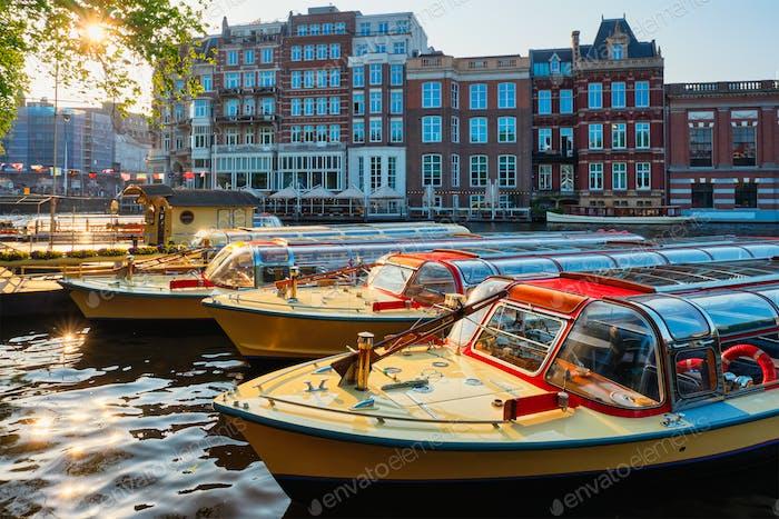 Touristenboote am Amsterdamer Kanalpier bei Sonnenuntergang festgemacht