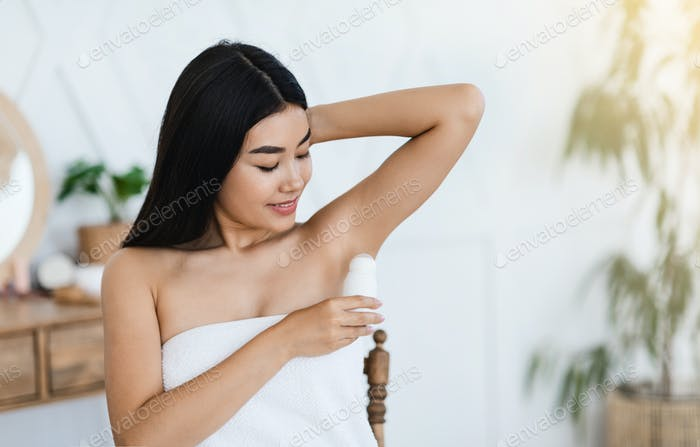 Young asian woman using deodorant in bedroom
