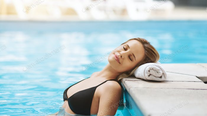 Calm young woman with closed eyes relaxing in swimming pool, empty space