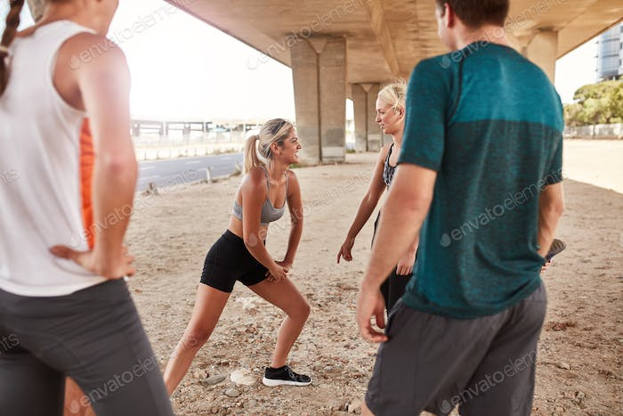 Woman with running club group stretching after a run