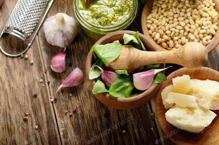 Draufsicht der Pesto-Sauce Zutaten und Utensilien auf Holztisch