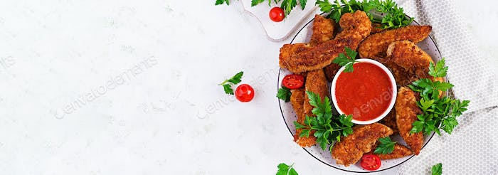 Breaded mini chicken fillets served with tomato sauce.