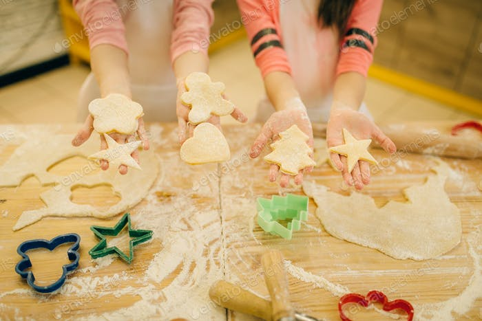 Little chefs show dough cut out by cookie cutters