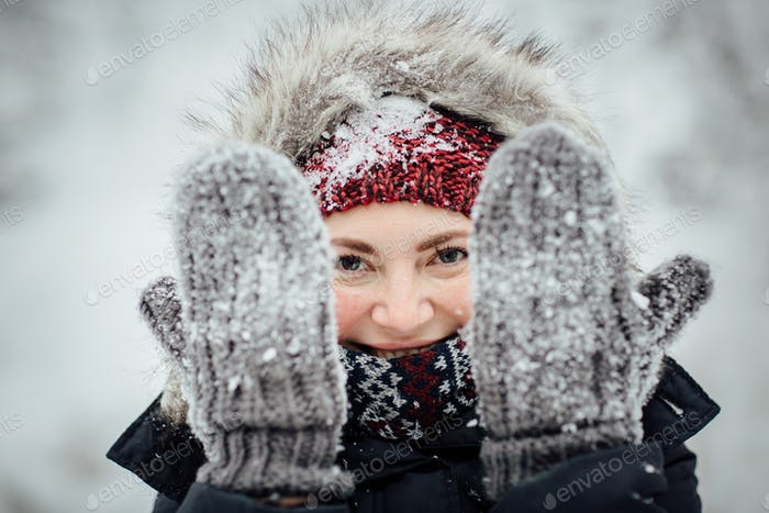 Female tourist with snow all over peeking through snowy gloves