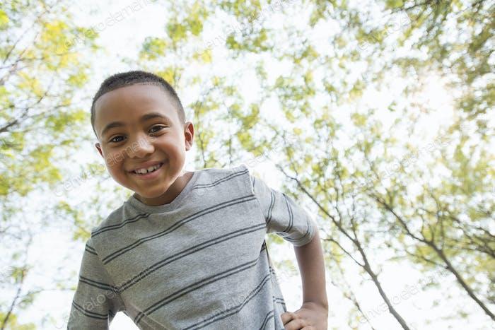 Ein Junge mit den Händen auf den Hüften blickt in die Kamera.