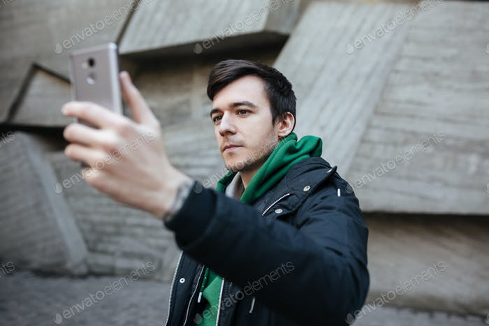 Portrait of young man in green sweatshirt thoughtfully looking in his cellphone