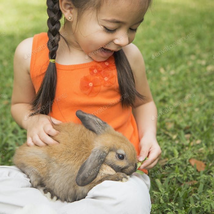 Ein Kind mit einem braunen Kaninchen auf dem Schoß.
