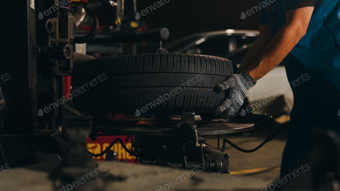 Professional car mechanic changing a car tire on lifted automobile at repair service station.