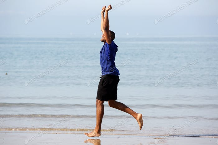 Side portrait of overjoyed black man running on sea shore with arms raised