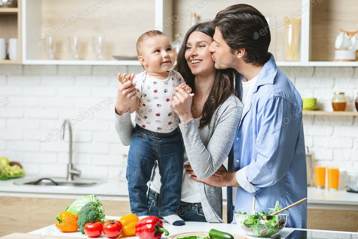 Young family embracing with baby at kitchen, empty space