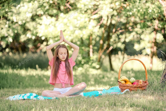 Little girl in yoga position in the park