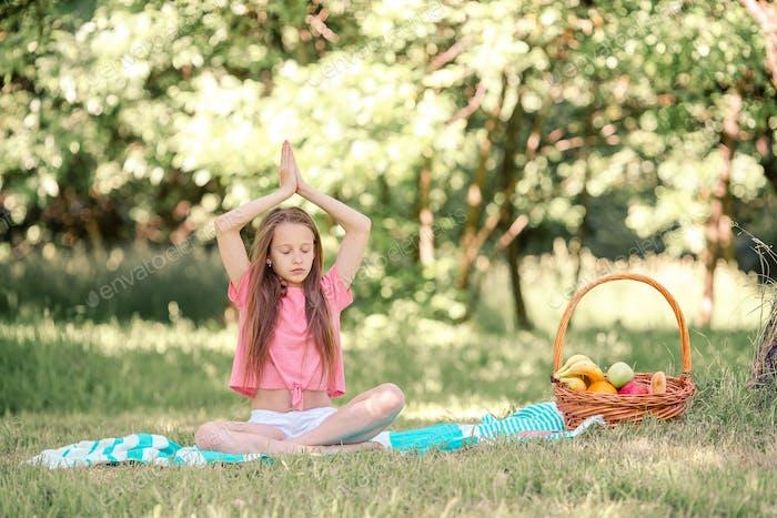 Kleines Mädchen in Yoga-Position im Park