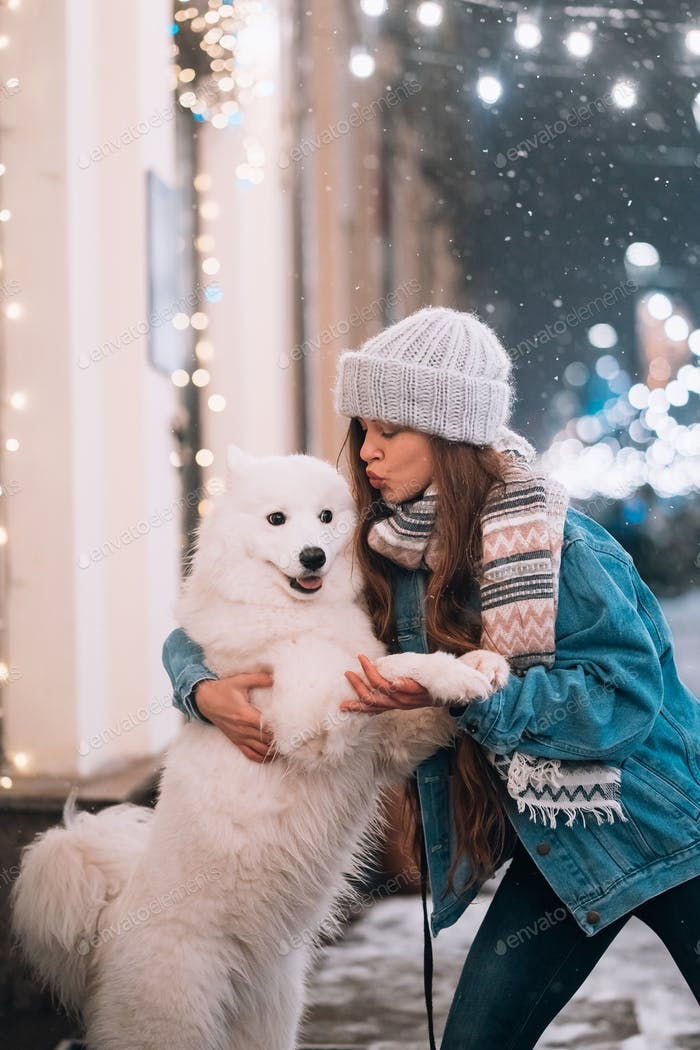 A woman is hugging her dog on a night street