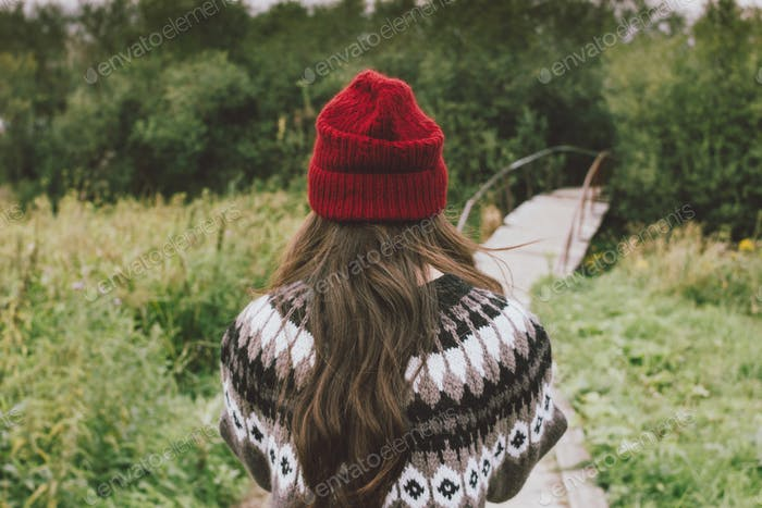 Long hair asian girl in red hat and knitted nordic sweater in autumn nature park