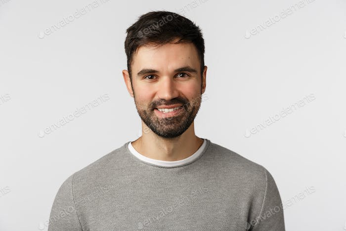 Motivated cheerful and glad, pleasant caucasian adult bearded man in grey sweater, smiling with