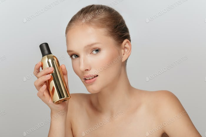 Portrait of young beautiful woman without makeup holding cosmeti