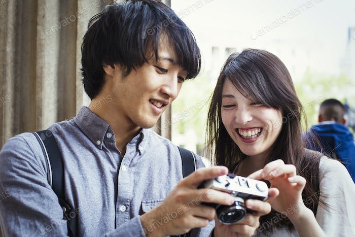 Young Japanese man and woman enjoying a day out in London, holding at a digital camera, smiling.
