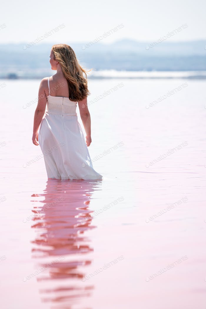 Back view of cute teenager woman wearing white dress standing on an amazing pink lake