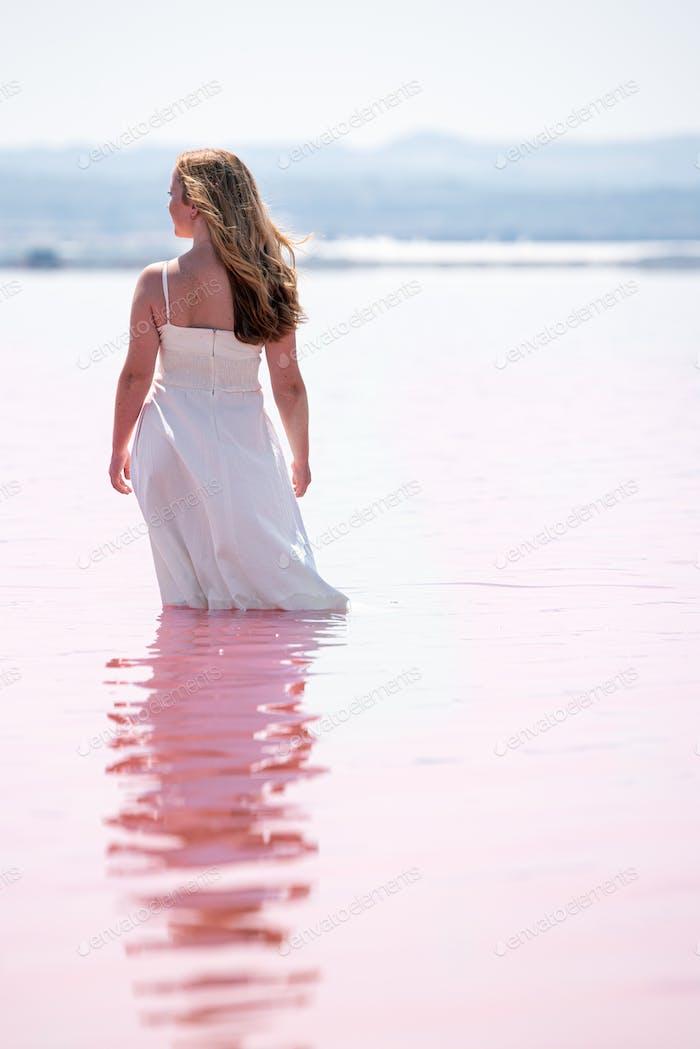 Rückansicht von niedlichen teenager Frau tragen weißes Kleid stehend auf einem erstaunlichen rosa See