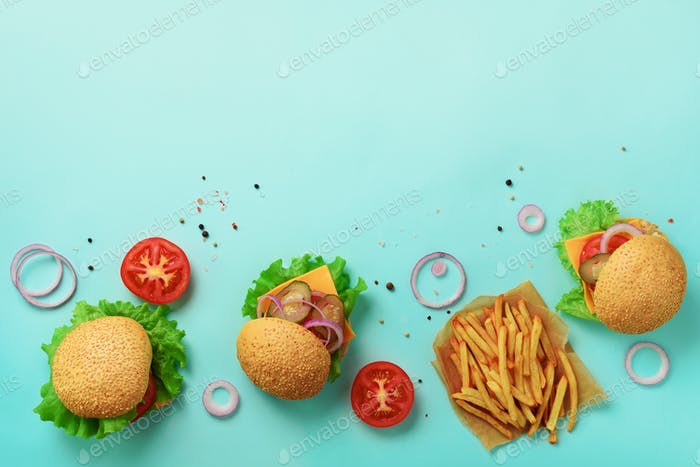 Tasty burgers with beef, tomato, cheese, onion, cucumber and lettuce on blue background. Top view