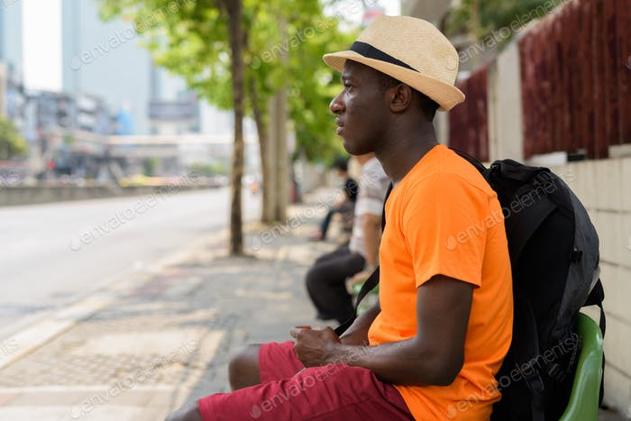 Young happy black African tourist man sitting at bus stop