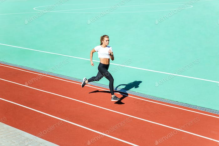 Female jogger running at stadium