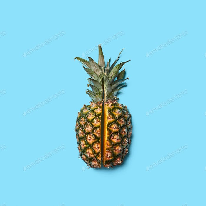Cut half, pineapple with green leaves on a blue background with space for text.Tropical healthy