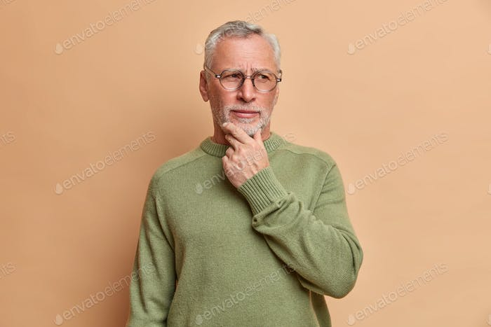 Pensive serious old bearded man holds chin and looks away thoughtfully thinks over received suggesti