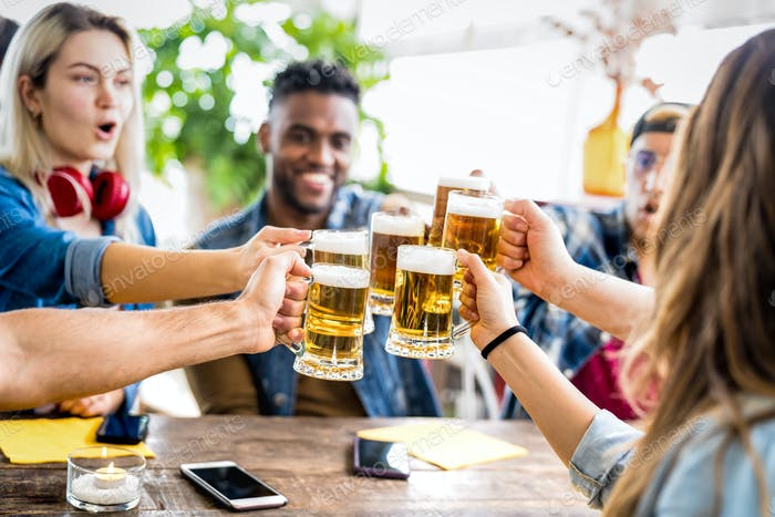 Happy multiracial friends drinking and toasting beer at brewery bar