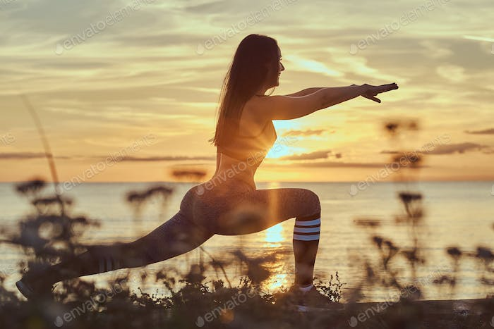 Fitness woman practicing stretching yoga exercises in nature