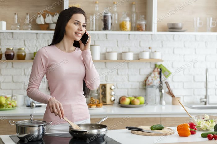 Young woman talking on phone and cooking lunch at kitchen