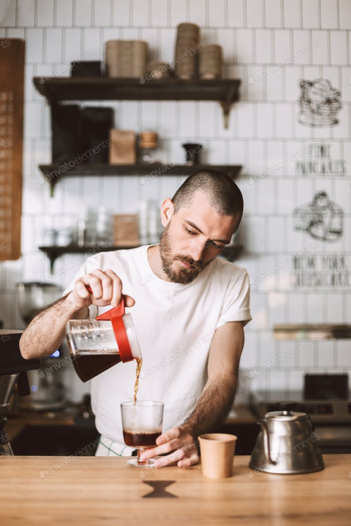 Young barista standing at bar counter and pouring filter coffee in glass in cafe