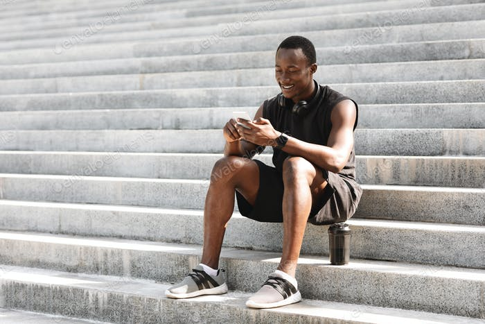 Sporty black guy using smartphone after training outdoors, sitting on urban stairs