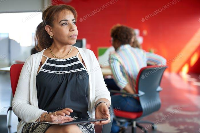 Selbstbewusste weibliche Chefin arbeitet auf einem digitalen Tablet in roten kreativen Büroflächen