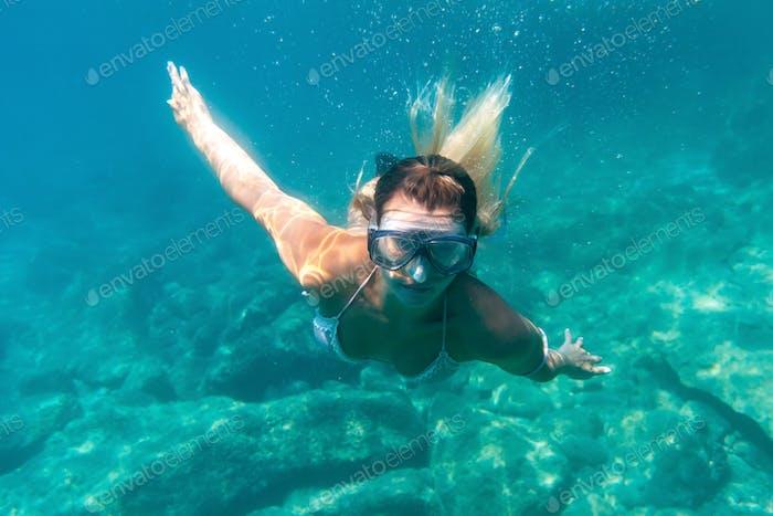 Frauen tauchen im tropischen Wasser, schnorcheln mit Maske