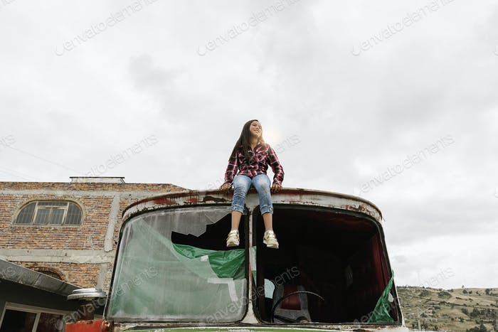 Cute girl playing on the abandoned truck.