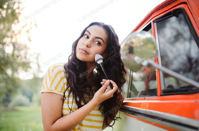 A girl looking in mirror and applying makeup on a roadtrip through countryside.