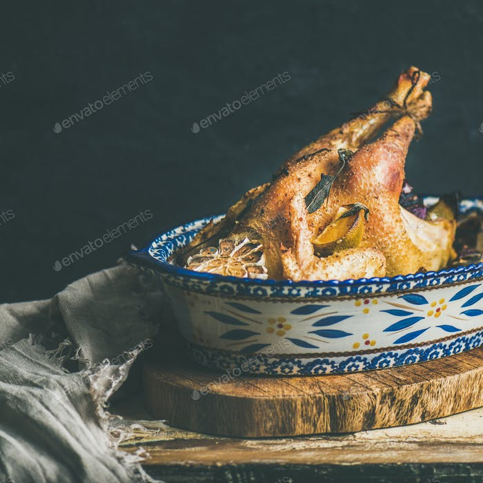 Roasted whole chicken for Christmas, black wall background, copy space