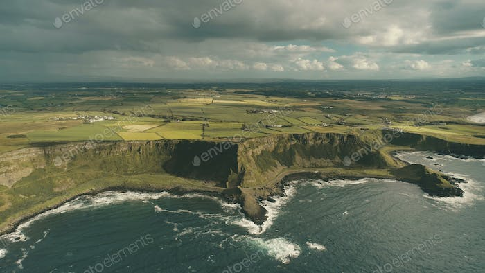Cliff ocean Ireland coast aerial view: green grass meadows with little cottages in farmland