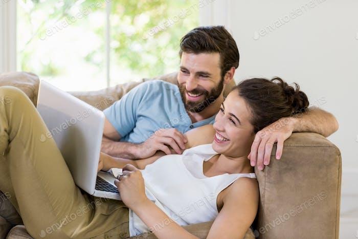 Happy couple lying on sofa and using laptop