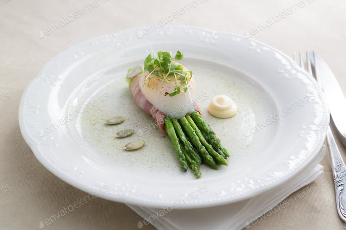 Green asparagus with poached egg on a plate