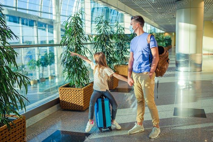Papá y niña con máscaras nedicales en el aeropuerto. Protección contra Coronavirus y Gripp
