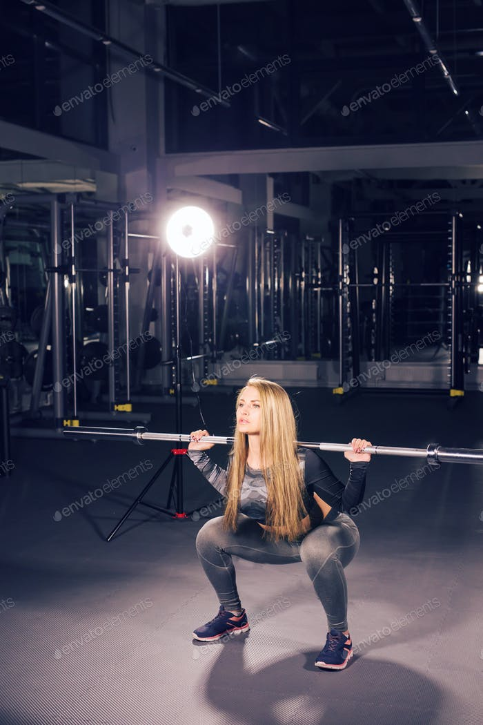 Pretty woman working out with barbell in a gym